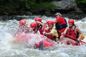 group laughing while white water rafting