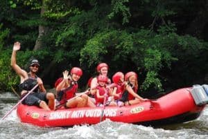 Family smiling whike white water rafting in the Smoky Mountains