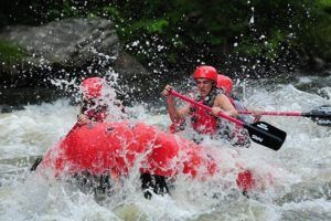 People paddling through the rapids on an Upper Pigeon River rafting trip.