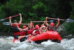 A Gatlinburg TN white water rafting group holding their paddles above their heads.