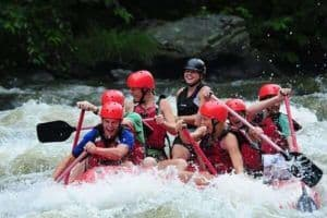 A happy group of friends white water river rafting on their Smoky Mountain vacation.