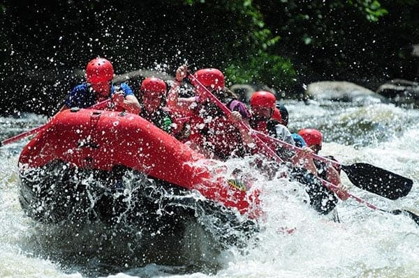 A family whitewater rafting with Smoky Mountain Outdoors.