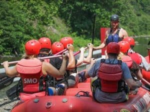 A rafting guide faces his passengers in his raft.