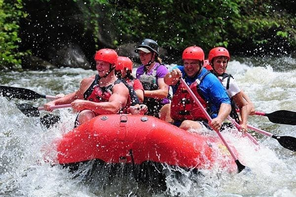 Happy group of people white water rafting in the Smokies.